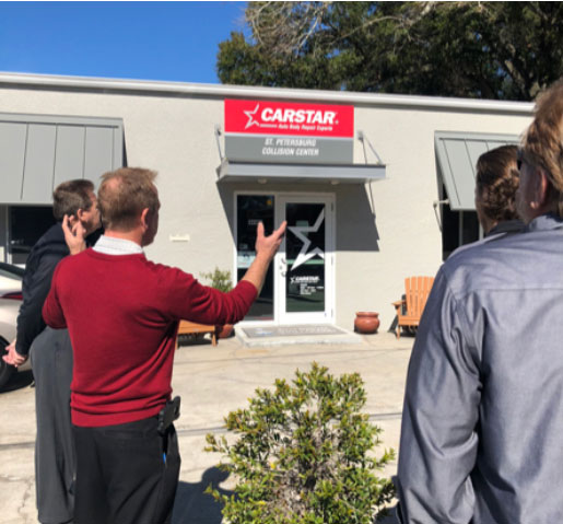 A man talking to a group in front of a CARSTAR location